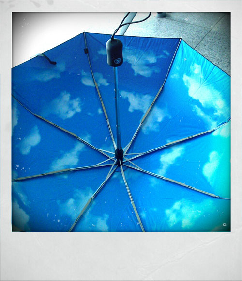 Inside of umbrella which is printed to look like a blue sky with clouds